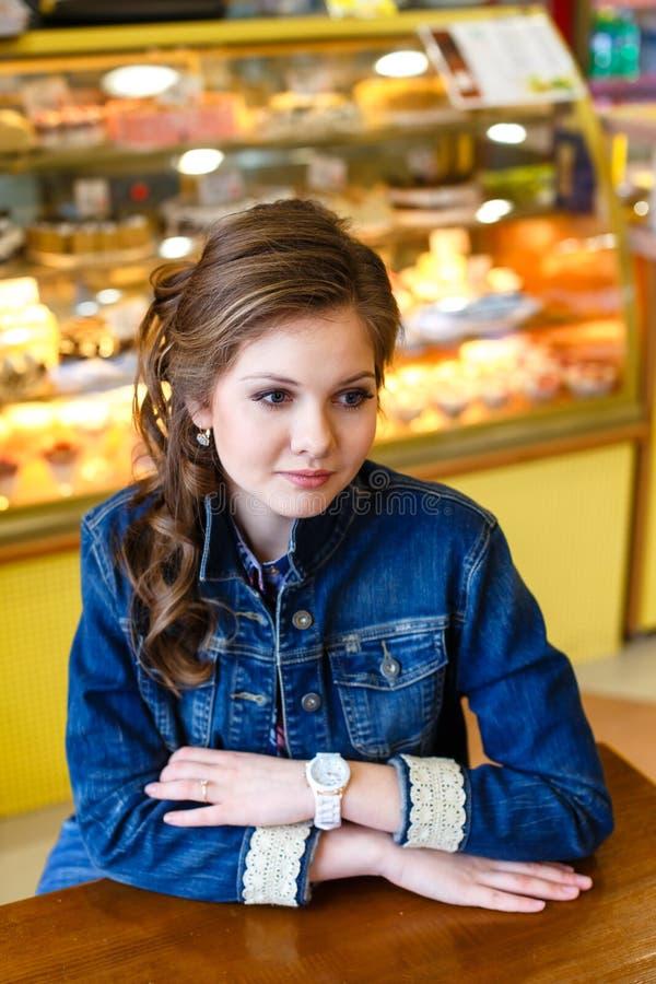 Menina de sorriso bonita com o cabelo louro longo que senta-se no café fotos de stock