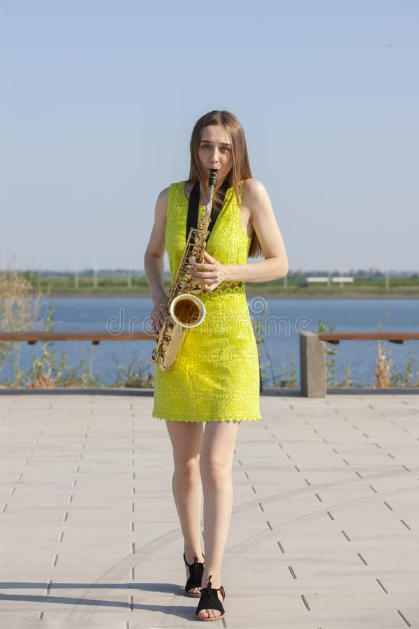 Menina de sorriso bonita com saxofone Saxofonista bonito novo com o saxofone - exterior na natureza imagem de stock
