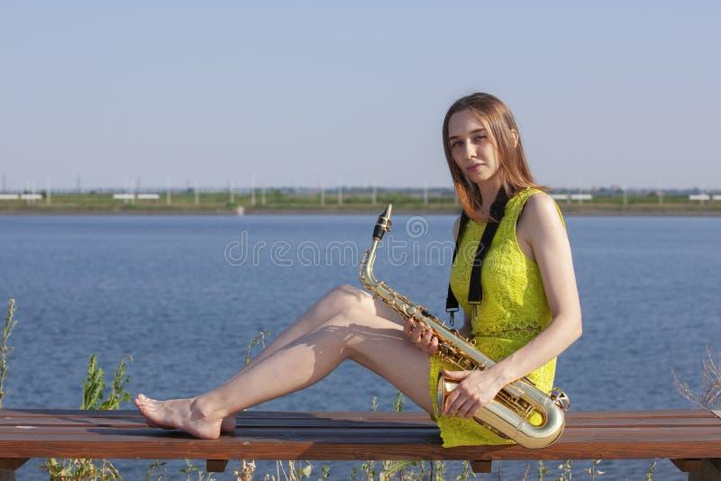 Menina de sorriso bonita com saxofone Saxofonista bonito novo com o saxofone - exterior na natureza fotos de stock royalty free