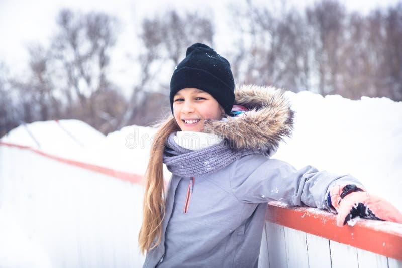 Menina de sorriso bonita da criança do inverno que anda no parque nevando durante feriados de inverno foto de stock