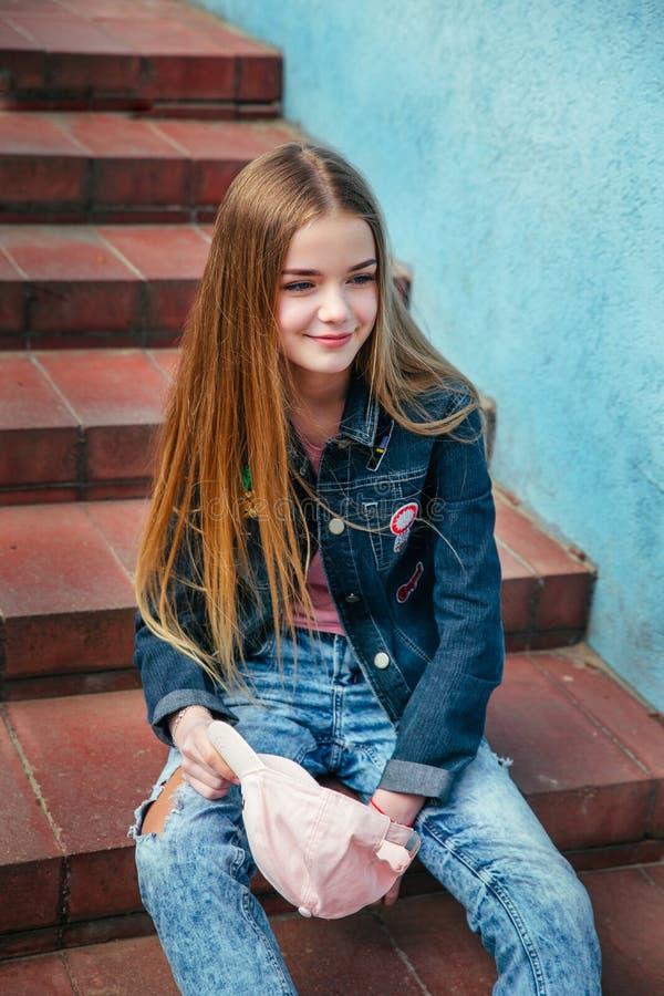 Menina de sorriso bonita do adolescente do close up do retrato com o revestimento do chapéu e da sarja de Nimes que senta-se na e fotos de stock