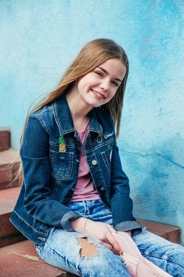 Menina de sorriso bonita do adolescente do close up do retrato no revestimento do chapéu e da sarja de Nimes sobre a parede azul imagem de stock
