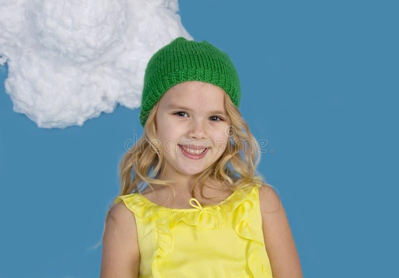 Menina de sorriso bonita em um tampão verde imagem de stock royalty free