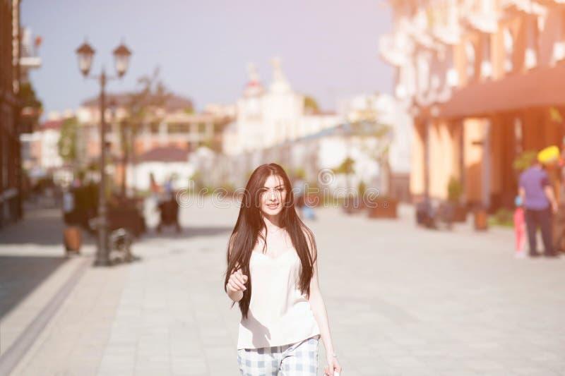 Menina de sorriso bonita feliz que anda na rua da cidade no dia de verão ensolarado fotografia de stock
