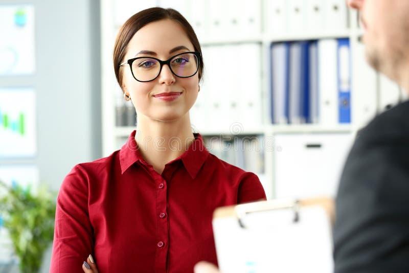 Menina de sorriso bonita na blusa vermelha no olhar do local de trabalho in camera fotos de stock royalty free