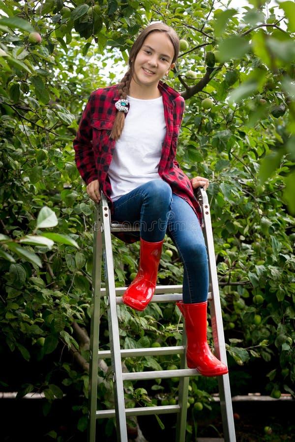 Menina de sorriso bonita nas botas de borracha vermelhas que sentam-se na escada portátil no jardim imagens de stock