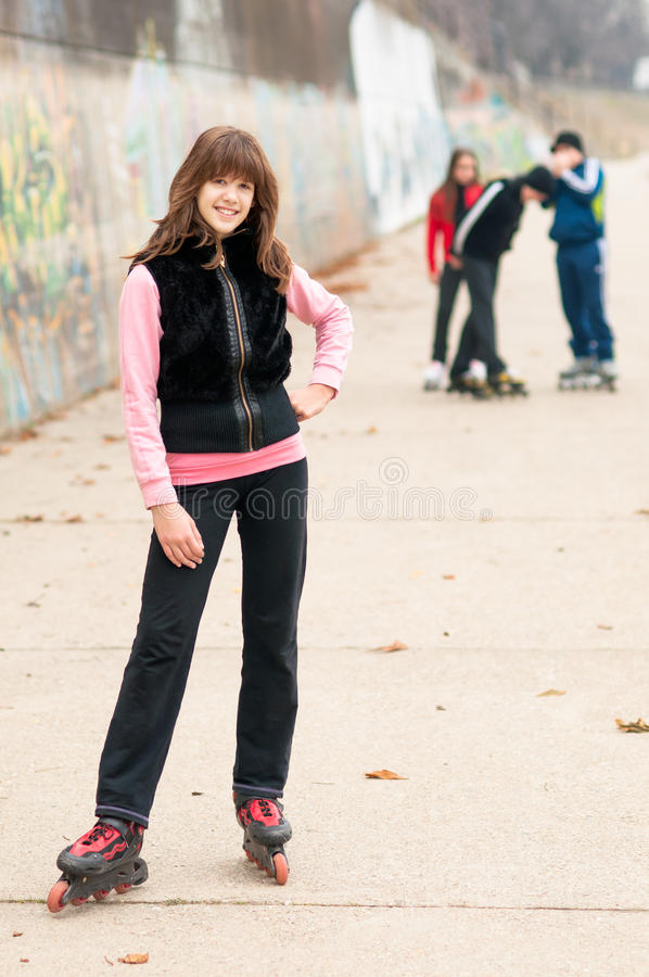 Menina de sorriso bonita no levantamento dos rollerskates exterior com amigos imagem de stock
