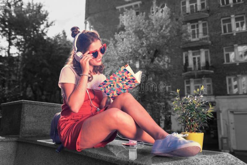 Menina de sorriso bonita que aprecia o dia ensolarado quando livro de leitura que senta-se fora fotos de stock