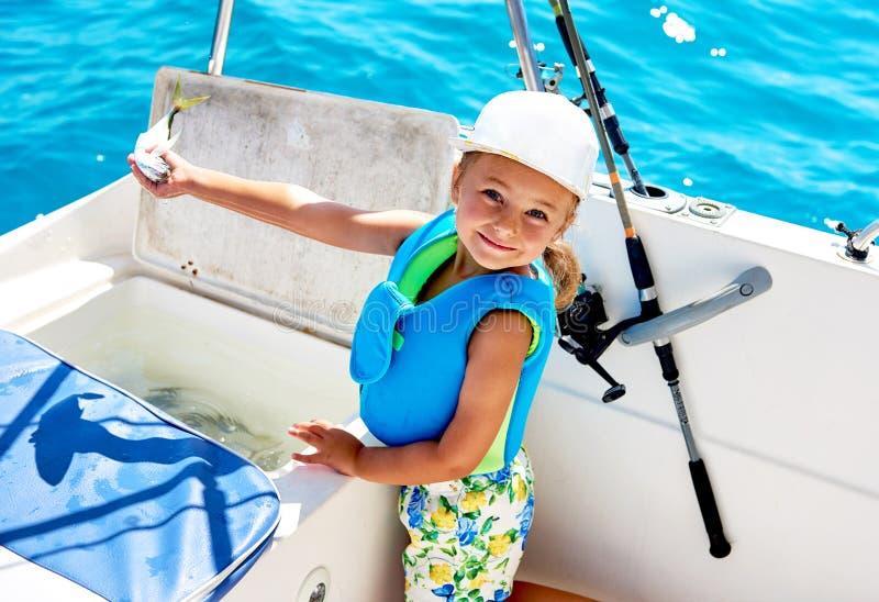 Menina de sorriso bonita que guarda um peixe fotografia de stock royalty free