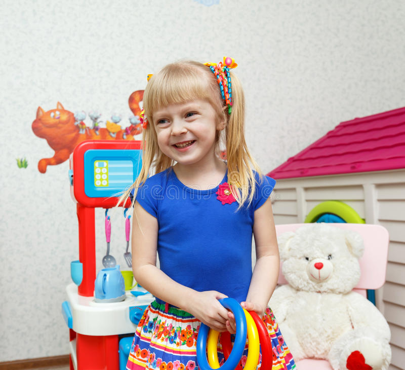 Menina de sorriso bonita que joga com os brinquedos na guarda imagem de stock royalty free
