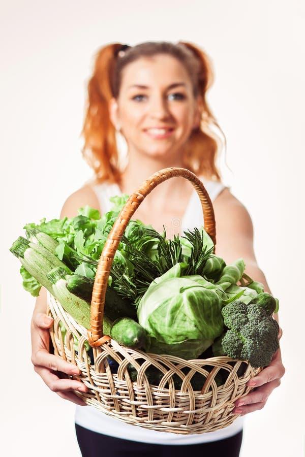 Menina de sorriso bonita que mantém a cesta de vegetais verdes crus frescos isolada fotos de stock