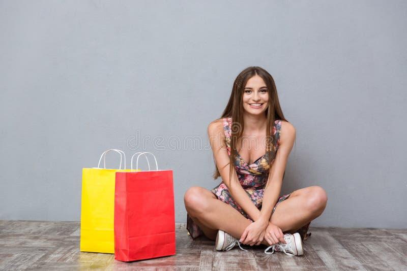Menina de sorriso bonita que senta-se no assoalho com os pés cruzados fotos de stock royalty free