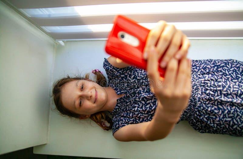 Menina de sorriso bonita que toma o selfie no smartphone ao encontrar-se na cama macia imagem de stock royalty free