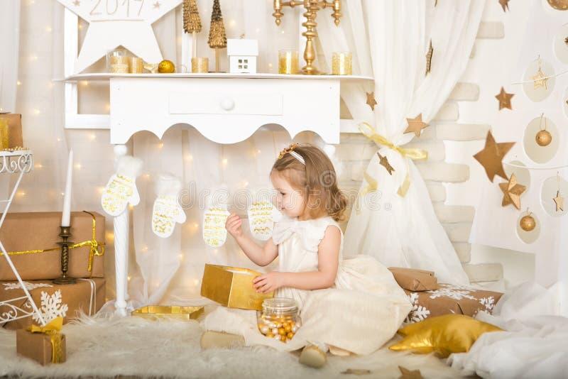 Menina de sorriso bonito com doces do ouro foto de stock
