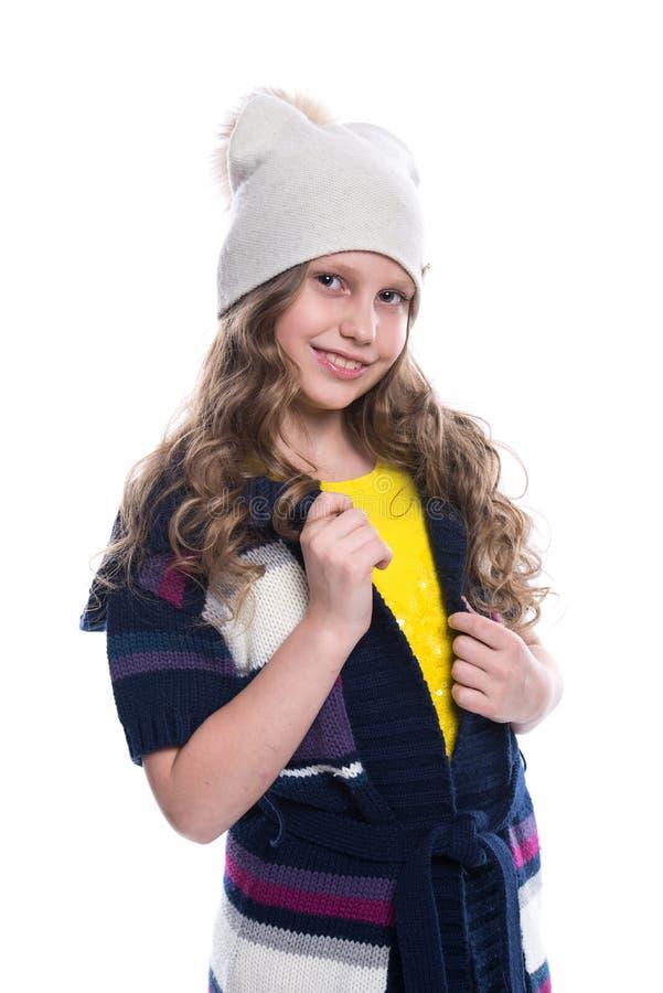 Menina de sorriso bonito com o penteado encaracolado que veste a camiseta, a camisa, calças coloridas e o chapéu isolados no fund imagens de stock royalty free