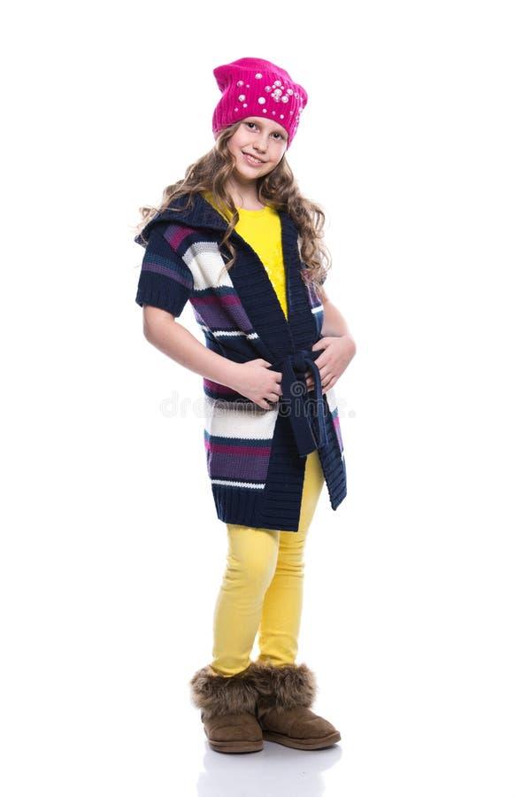 Menina de sorriso bonito com o penteado encaracolado que veste a camiseta, a camisa, calças coloridas e o chapéu isolados no fund imagens de stock