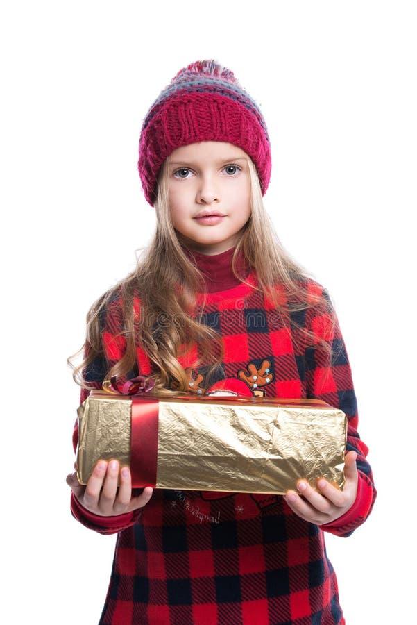 Menina de sorriso bonito com o penteado encaracolado que veste a camiseta, o lenço feito malha e o chapéu mantendo o presente do  foto de stock royalty free