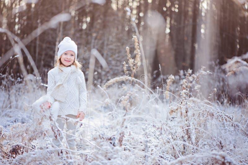 Menina de sorriso bonito da criança na caminhada na floresta congelada inverno imagem de stock royalty free
