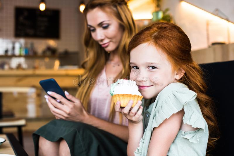 menina de sorriso bonito do ruivo que come o queque quando utilização da mãe imagens de stock royalty free