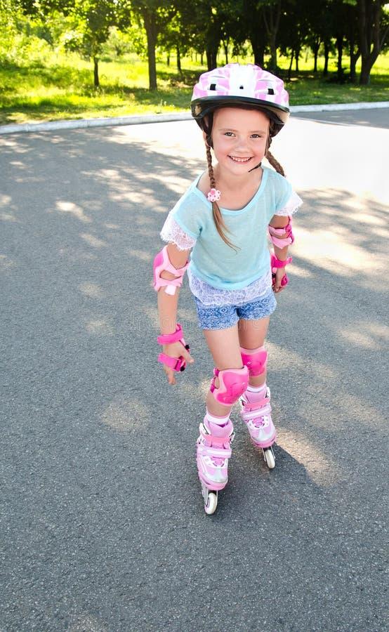 Menina de sorriso bonito em patins de rolo cor-de-rosa fotografia de stock