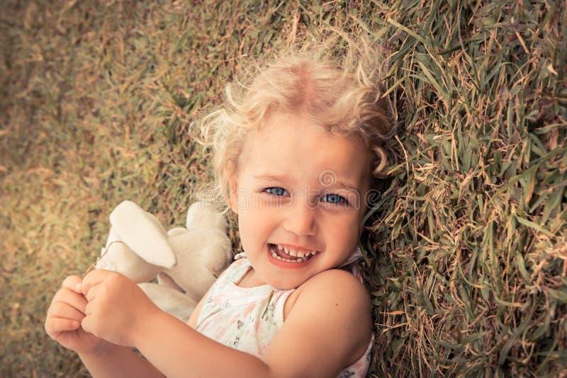 Menina de sorriso bonito feliz da criança com os olhos bonitos que encontram-se no estilo de vida despreocupado da infância da fe foto de stock royalty free