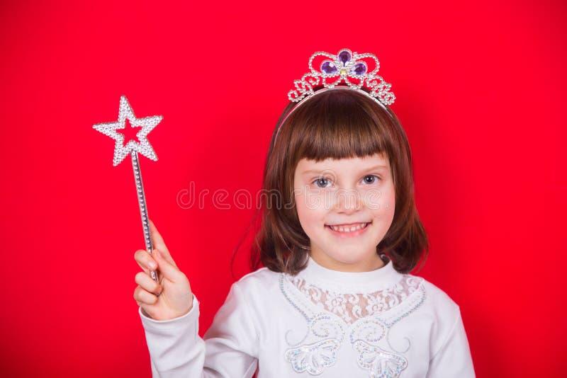 A menina de sorriso bonito no traje do Natal da varinha mágica guardando feericamente com protagoniza no estúdio no fundo vermelh imagens de stock royalty free