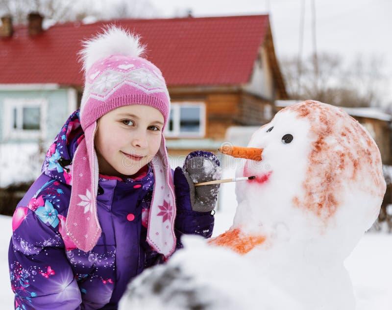 A menina de sorriso bonito pinta um boneco de neve fotografia de stock royalty free