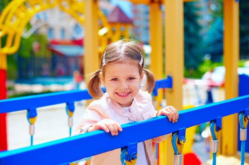 Menina de sorriso bonito que joga no pré-escolar, no campo de jogos fotografia de stock