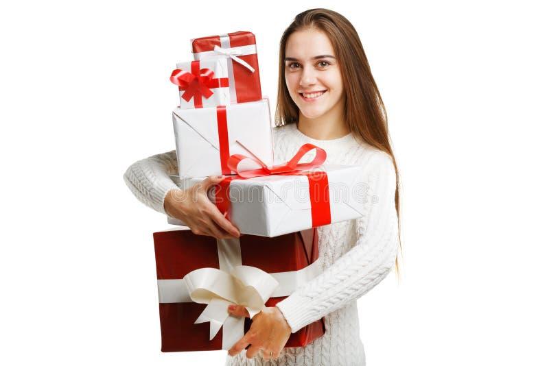Menina de sorriso bonito que mantém o presente do Natal isolado no fundo branco Conceito do feriado foto de stock