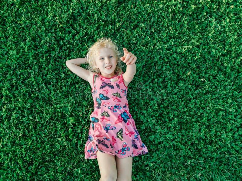 Menina de sorriso caucasiano loura no vestido cor-de-rosa vermelho que encontra-se na grama que aponta com dedo foto de stock royalty free