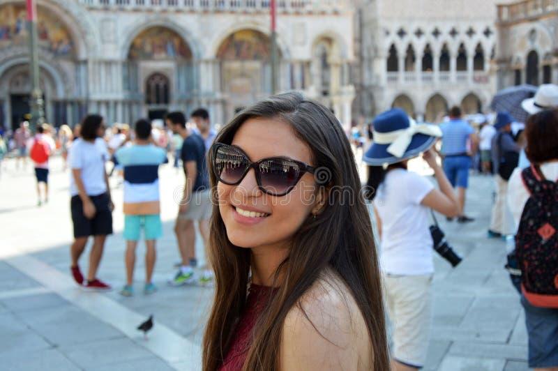 Menina de sorriso com óculos de sol, modelo da mulher, no quadrado Veneza do ` s de St Mark com turistas e na igreja na parte inf imagens de stock royalty free