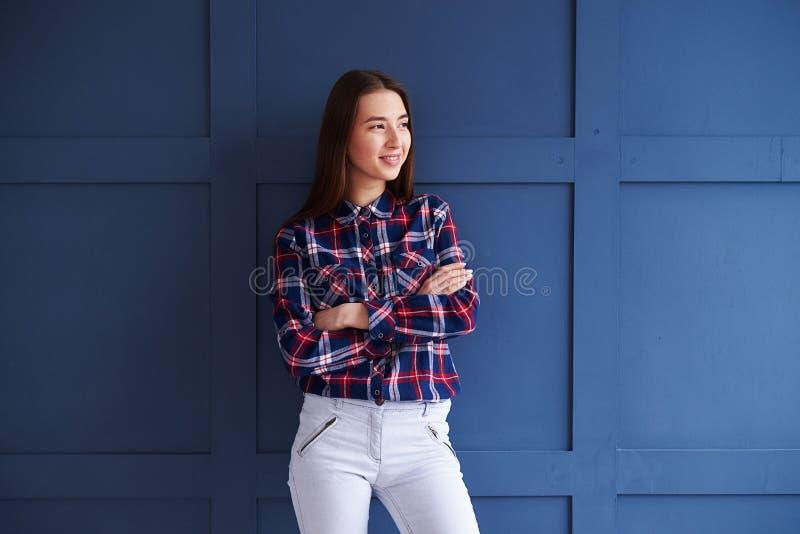Menina de sorriso com as mãos cruzadas que olham de lado imagens de stock