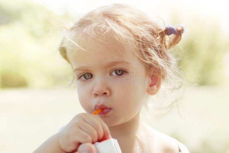 A menina de sorriso com as tranças engraçadas como Pippi bebe o suco de laranja fresco imagens de stock