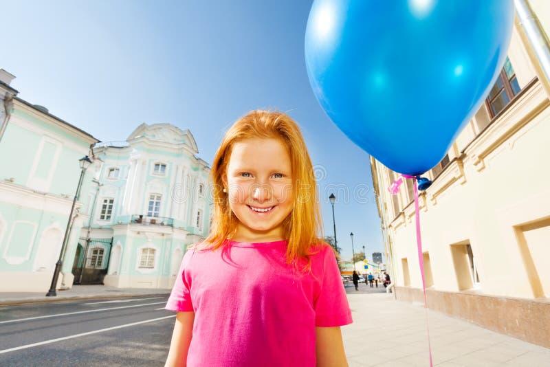 A menina de sorriso com balão do voo está na rua fotografia de stock royalty free