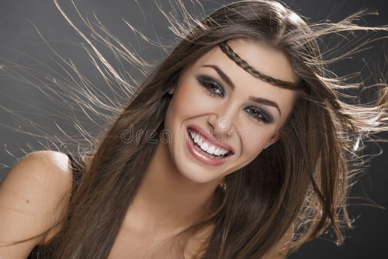 Menina de sorriso com cabelo de sopro imagem de stock
