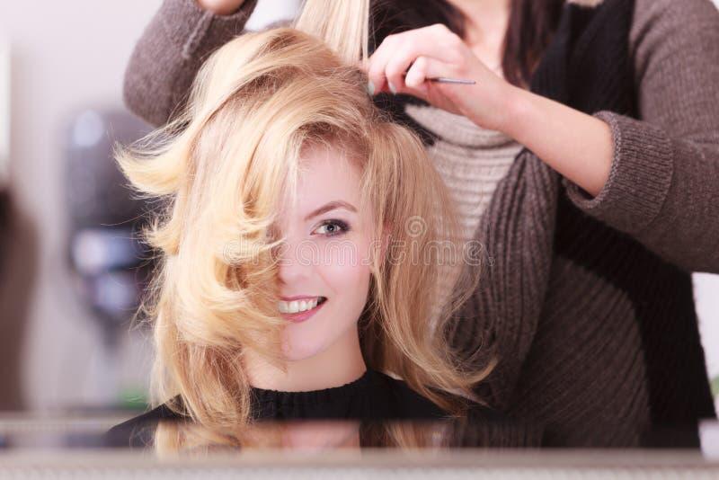 Menina de sorriso com cabelo ondulado louro pelo cabeleireiro no salão de beleza imagens de stock royalty free