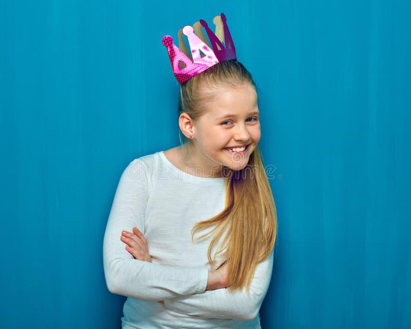 Menina de sorriso com a coroa de papel que está com os braços cruzados foto de stock