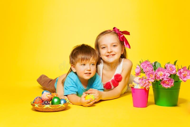 Menina de sorriso com a criança pequena que encontra-se no assoalho fotos de stock