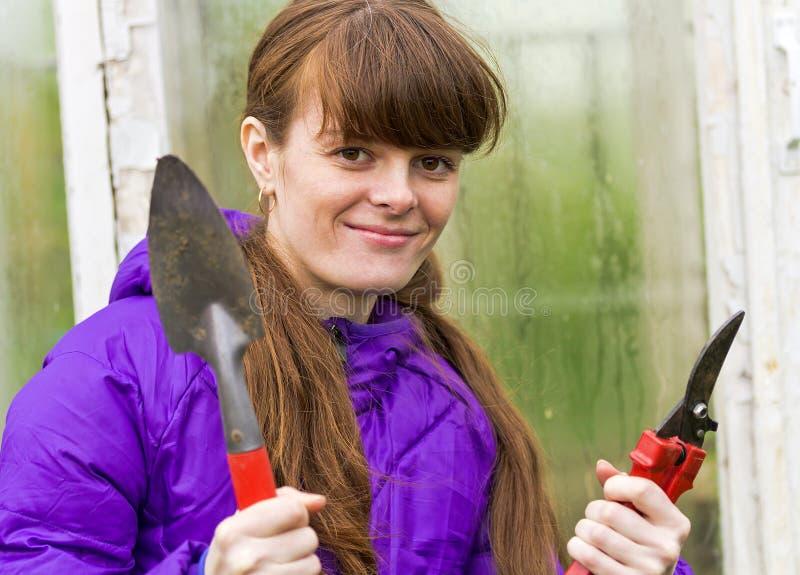 Menina de sorriso com ferramentas de jardim à disposição imagem de stock
