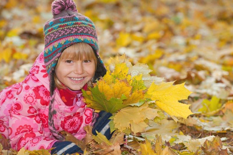 Menina de sorriso com folhas amarelas imagem de stock royalty free