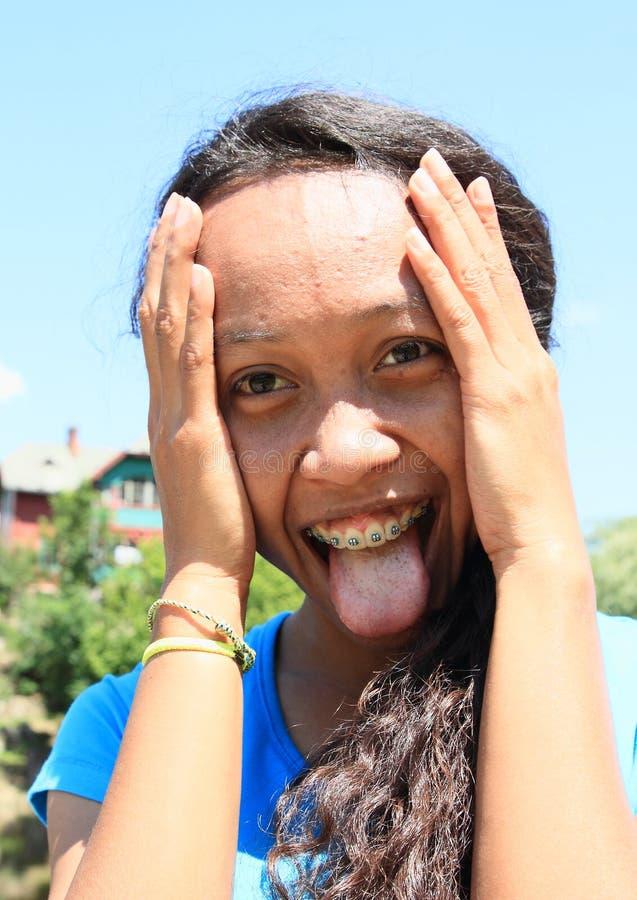 Menina de sorriso com língua de projeção fotos de stock