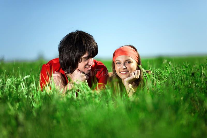 Menina de sorriso com o menino na grama imagem de stock royalty free