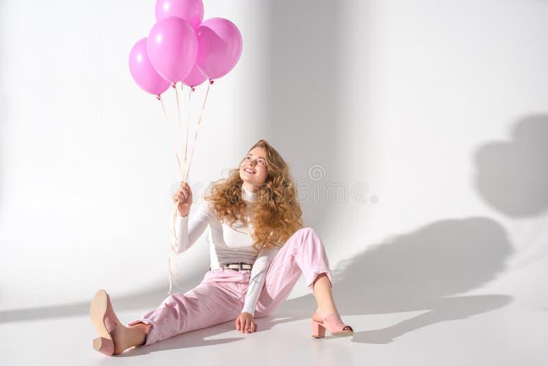 menina de sorriso com o pacote de assento cor-de-rosa dos balões fotografia de stock