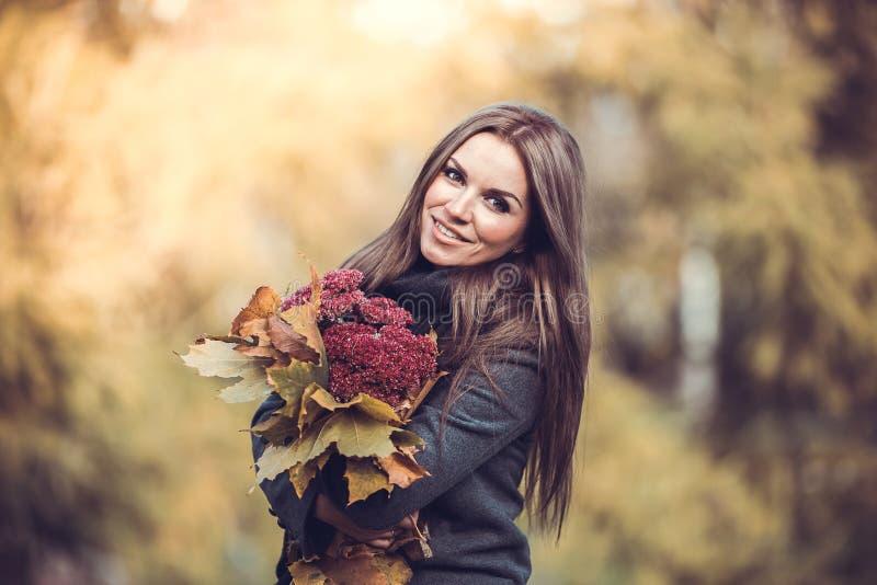 Menina de sorriso com o ramalhete no parque do outono imagem de stock royalty free