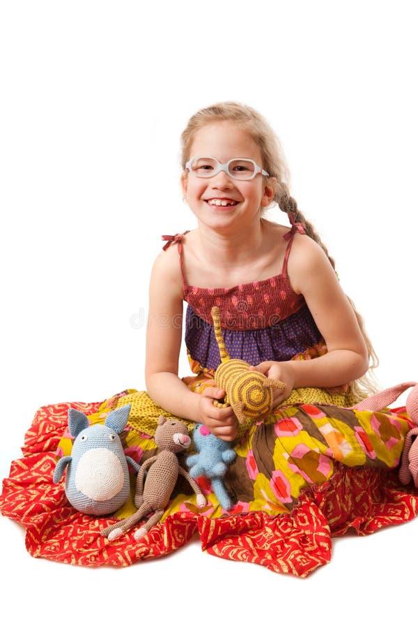 Menina de sorriso com os brinquedos caseiros feitos malha foto de stock