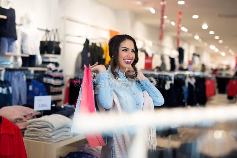 Menina de sorriso com os sacos de compras na loja imagens de stock royalty free