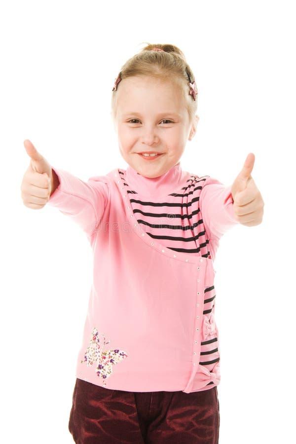 A menina de sorriso com polegares levanta o sinal fotografia de stock