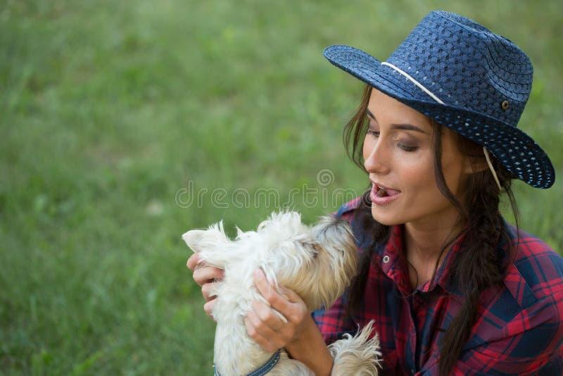 Menina de sorriso com seu cão pequeno chapéu de vaqueiro e camisa de manta fotografia de stock royalty free