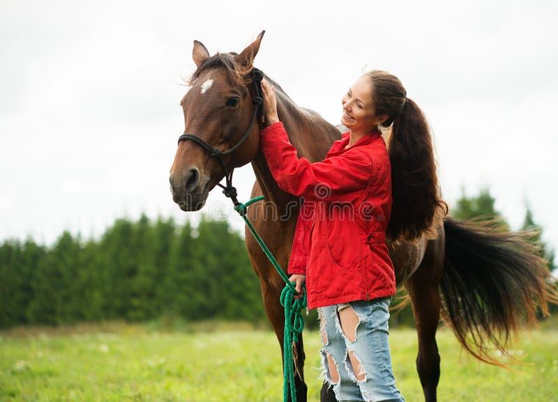 Menina de sorriso com seu cavalo marrom imagens de stock royalty free