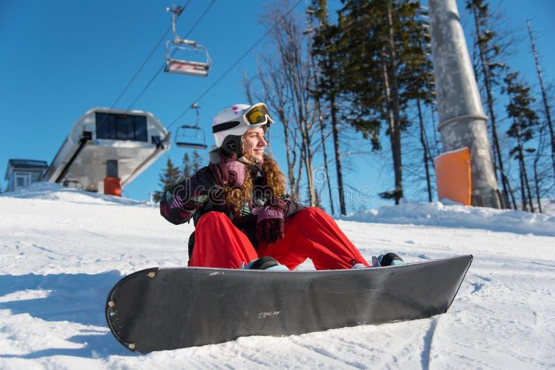 A menina de sorriso com snowboard senta-se na neve em raios do sol fotografia de stock royalty free